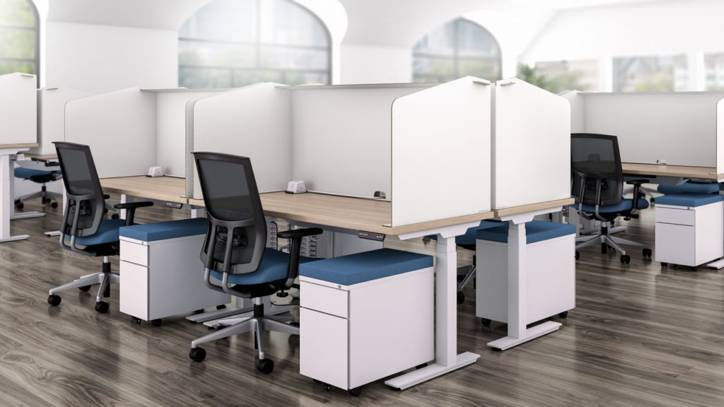 An office with multiple white cubicles with rolling chairs and blue accents by OFDC Commercial Interiors
