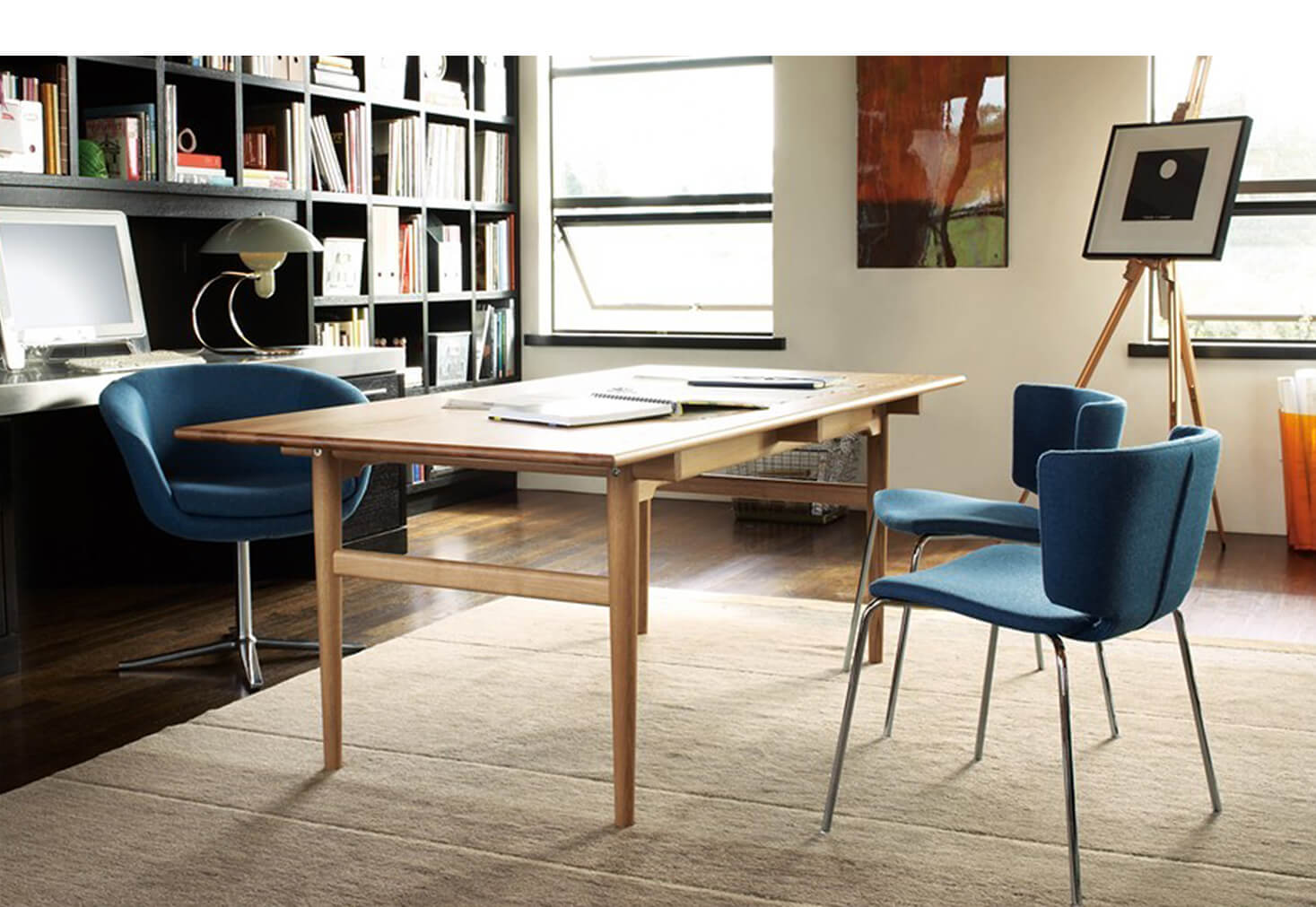 A long table in between 3 blue chairs in front of a book shelf by OFDC Commercial Interiors
