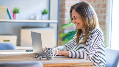 woman smiling while working from home on her computer