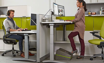 2 people working in an office by OFDC Commercial Interiors. Woman is at standing desk