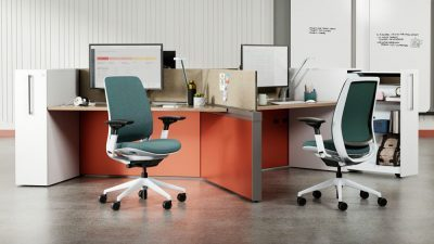 2 desks with computers on them and 2 green rolling chairs by OFDC Commercial Interiors