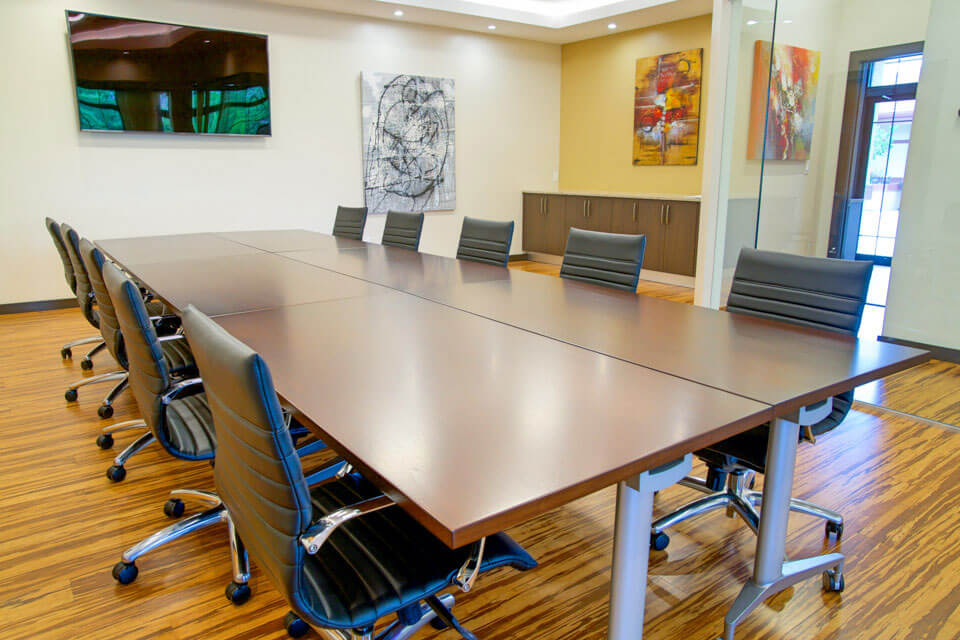 6 tables pushed together form a conference table with 10 black office chairs and wood flooring by OFDC Commercial Interiors