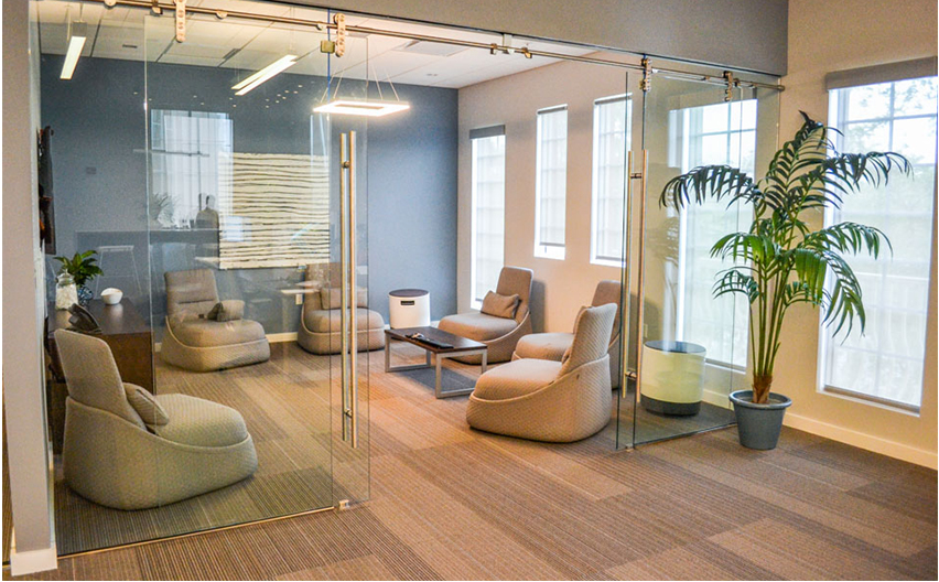 OFDC Commercial Interiors modern meeting room with six low taupe chairs, soft blue wall and glass barn doors
