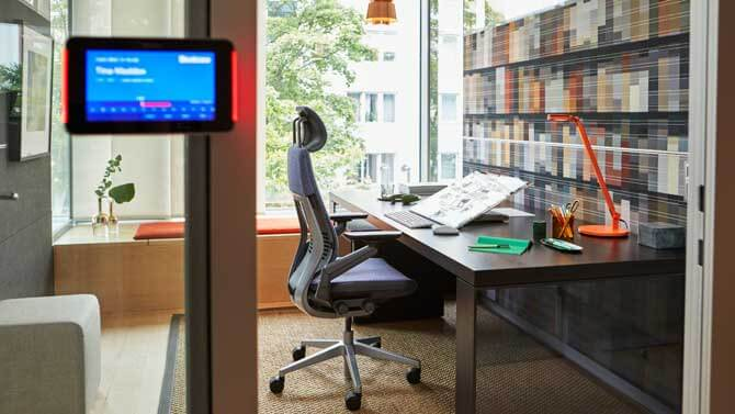 A modern office with a rolling chair and desk in front of a window